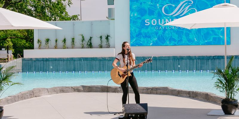Live acoustic guitar player and singer in front of SoundWaves pool at screen
