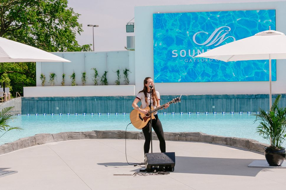 Acoustic Guitar Player in front of pool movie screen - SoundWaves Live Entertainment